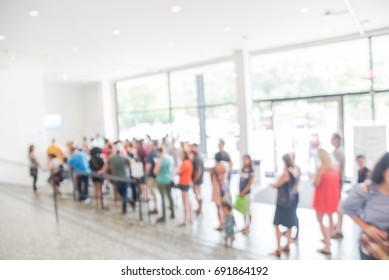 Blurred long people queuing at check-in counter museum entrance in Houston, Texas, US. Abstract background large group of diverse multiethnic visitors crowd family member, adult, kid, toddler waiting
