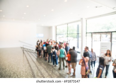 Blurred long people queuing at check-in counter entrance of museum in Houston. Abstract large group of diverse multiethnic visitors crowd family member, adult, kid, toddler waiting in separation line.