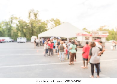Blurred long people queuing for check-in at public event in Houston, Texas, US. Abstract background large group of diverse multiethnic visitors crowd family member, adult, kid waiting at tent entrance