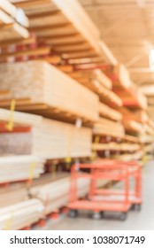 Blurred lumber wholesale yard with divider cart at hardware store in America. Rack of fresh mill/cut wood timber in warehouse, pegboard, plywood, osb paneling, mdf. Industrial background