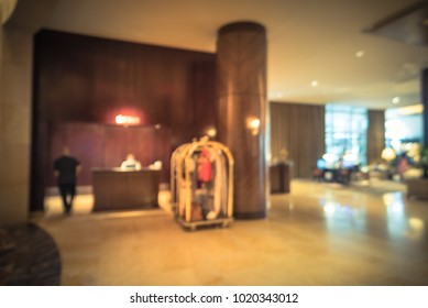 Blurred Luxury Lobby Reception Desk Interior, Hotel Luggage Cart And  Bellman. Vintage Tone.
