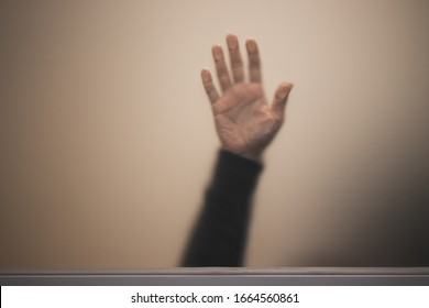 Blurred male hand behind matte glass wall, abstract photo