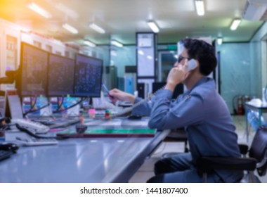 Blurred of man engineer works with the tablet in the production control room.Control room of a steam Turbine,Generators of the coal-fired power plant for monitor process, business and industry concept
