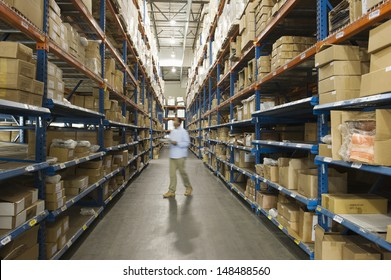Blurred man inspecting boxes in distribution warehouse