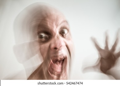 Blurred man suffering from dementia and insanity, opened hand, screaming, in moment of fury, hallucination