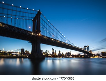 Blurred Manhattan Skyline and Manhattan Bridge At Night. Manhattan Bridge is a suspension bridge that crosses the East River in New York City