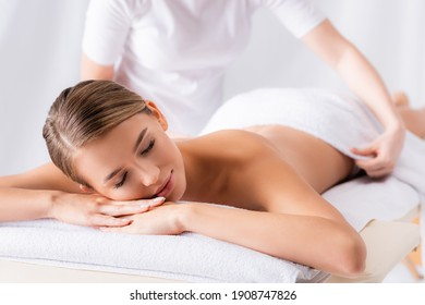 blurred masseur adjusting towel on client with closed eyes lying on massage table