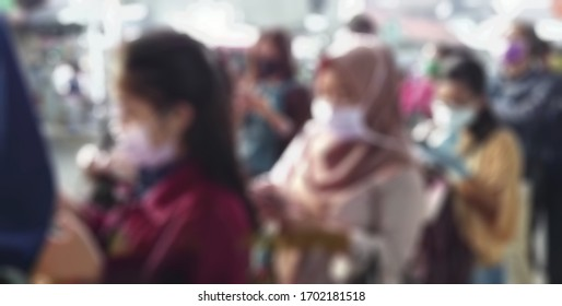 Blurred medical Worker uses a thermometer gun to check the temperature of people on public market for protect spreading covid 19 virus.