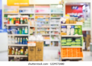 Blurred medicines arranged in shelves at pharmacy.