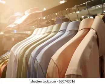 blurred mens shirts in different colors on hangers in a retail clothes store