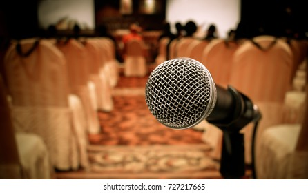 Blurred of microphones in seminar room, talking speech in conference hall light with microphone and keynote. Speech is vocalized form of communication humans, vintage tone.