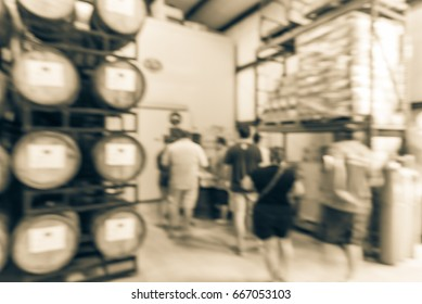 Blurred modern beer plant (brewery), stack of barrels in cellar, stainless steel brewing equipments and customers line up to taste craft beer in taproom. Brewery production vats, fermentation interior