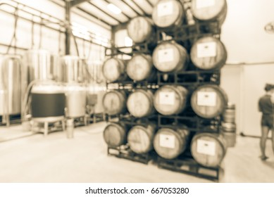 Blurred modern beer plant (brewery), stack of barrels in cellar, stainless steel brewing equipment and customers line up to taste craft in taproom. Production vats, fermentation interior. Vintage tone