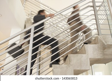 Blurred motion of businessmen moving upstairs in office