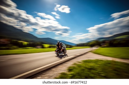 Blurred motion Couple Bikers riding a motorcycle on the road.