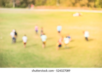 Blurred motion diverse group of young people in two opposing teams playing American football in the park meadow at Houston, Texas, US on Sunday sunny afternoon. Teamwork and healthy lifestyle concept.