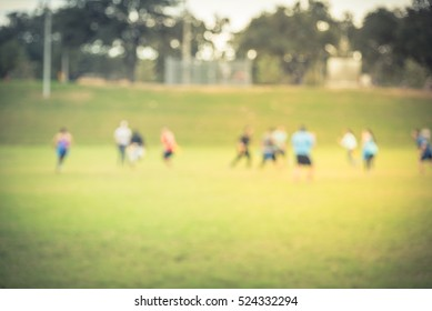 Blurred motion diverse group of young people in two opposing teams playing American football in the park meadow at Houston, Texas, US on sunny day. Teamwork and healthy lifestyle concept. Vintage tone