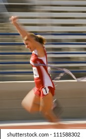 Blurred motion of excited female athlete runner crossing the finishing line