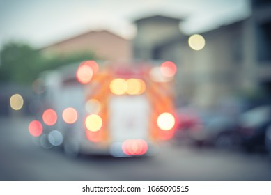 Blurred motion fire trucks at apartment incident in Texas, USA. Multi-floor residential building complex. Abstract background fire accident damage with bokeh lights, insurance concept. Vintage tone