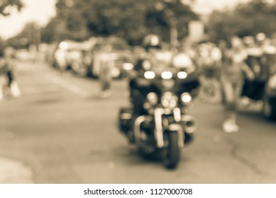 Blurred motion Fourth of July parade celebration in Irving, Texas, USA. Residents enjoy walking in groups, decorating floats vehicle and celebrate the nation founding, police motorcycle support