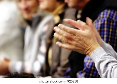 Blurred motion image (slow shutter speed) of a pair of hands clapping in a crowd.