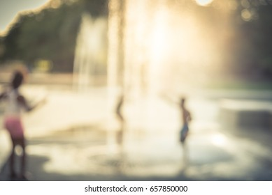 Blurred motion of kids having fun play with water at playground in summer time. Activities for children at outdoor aquatic park with water sprinkle and fountain at sunset. Amusement park. Vintage tone