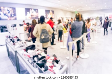 Blurred motion long line of diverse customers waiting to checkout at apparel, accessories store in Texas, USA. Defocused abstract crowed people retractable stanchions queue barrier, holiday shopping