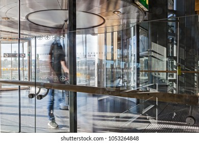 Blurred motion of a man walking through revolving doors at at a large building with sun streaming in from outside reflecting on the glass architecture of the modern and polished stone floor.