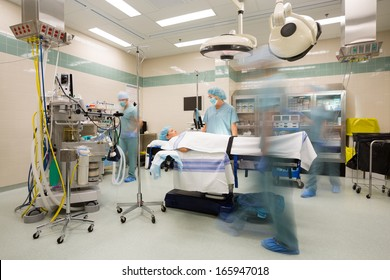 Blurred motion of nurses and surgeon preparing operating stuite for surgery