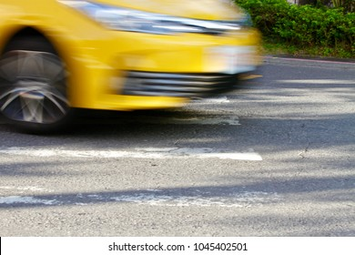 The blurred motion photo of a taiwan taxi driving across the pedesitrain