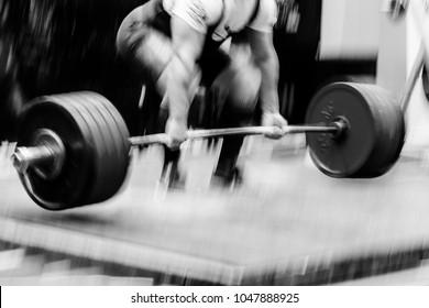 blurred motion powerlifter exercise deadlift heavy barbell