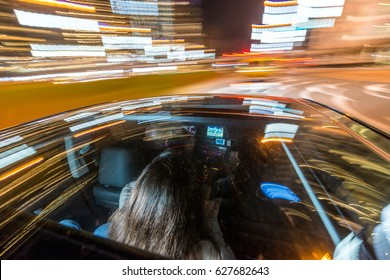 Blurred motion of professional taxi driver riding woman on illuminated city street at night