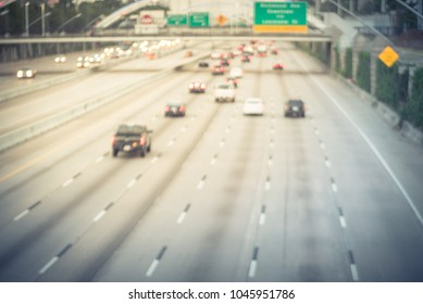 Blurred motion rush hour traffic on Interstate Highway 69 Houston. Aerial view traffic jam line of car peak travel times and street signs at sunset.  Freeway trench, long-span arched bridge. Vintage