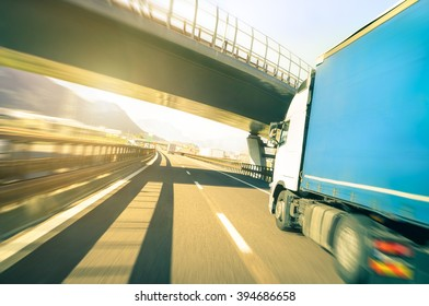 Blurred motion of semi truck speeding on highway under overpass - Transport logistic with semitruck container driving on speedway - Soft vintage filter with sunshine halo - Focus on further street end