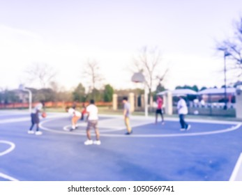 Blurred motion teen friends playing basketball at community park in Irving, Texas, USA. Sportive Afro-American, Hispanic young boys having friendly match outdoors. Urban basketball court background