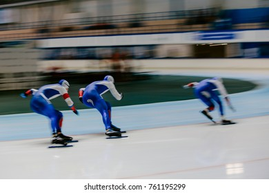 blurred motion three women athletes speed skaters in warm up