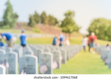 Blurred motion volunteers, family members place flags in front of each fallen heroes headstone. Memorial day celebration, honoring the legacy veterans Dallas–Fort Worth National Cemetery, USA