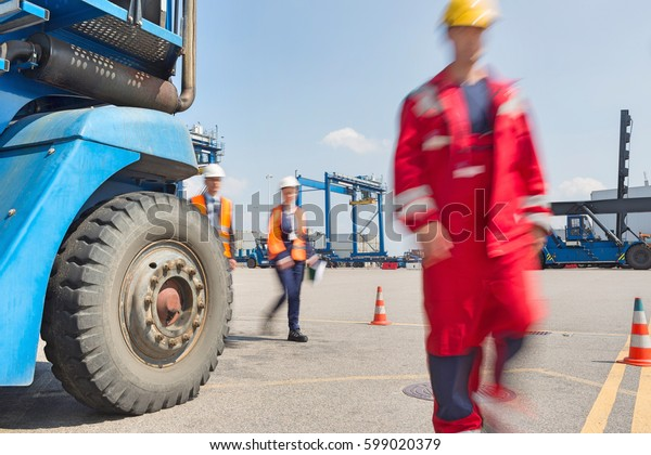 Blurred motion of workers walking in shipping yard
