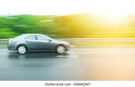 Blurred Motion,car moves very fast speed on highway with green tree