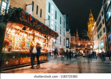 Blurred moved people and sales booth at the christmas market on Marienplatz against Town Hall Neues Rathaus in Munich, Germany