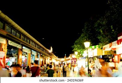blurred moving shopper at night bazaar market in thailand
