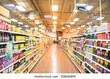 Blurred natural coffee, tea, water, bottled tea, energy drinks aisle in store at Houston, Texas, US. Wide view supermarket shelves, variety of products display with bokeh light. Customer shopping.