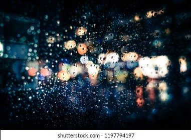 Blurred New York City street background with waterdrops, neon lights and cars at raining evening time
