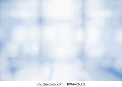 BLURRED OFFICE BACKGROUND, LIGHT BLUE BUSINESS HALL WITH BIG WINDOW AND LIGHT REFLECTIONS