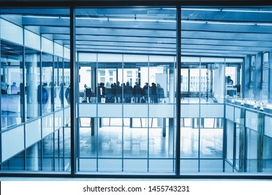 Blurred office interior space background. Large window into office. Conference background. Business People Cityscape Corporate Concept. Silhouette of business people.