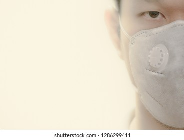 Blurred on purpose. Close up half face portrait of model with N95 respiratory mask isolated on smoke with copy space. Smog is a type of severe air pollution. Dangerous concept.