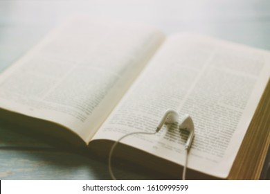 Blurred of open bible with phone and headphones,Concept listen the words of God