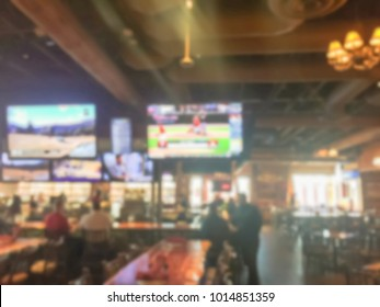 Blurred open space sport bar with large wall mount flat-screen TV, classic wooden table, chair. People drink craft beer, hanging out, resting, watching sport. Happy Hour and night club concept