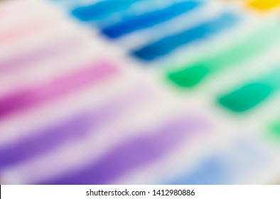 Blurred out of focus multi-colour watercolor swatches background - Close up of a hand painted color swatch artist chart with a pink blue and green spectrum on white canvas