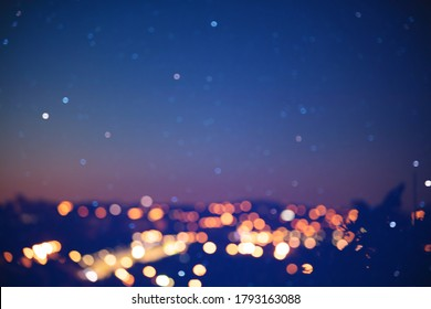 Blurred out of focus photo of city in dawn with star on the sky.